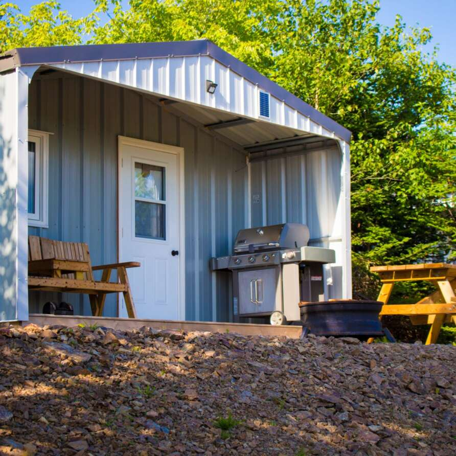 Metal clad cabin with porch, barbercue, deck chairs, picnic table and fire pit nestled in the forest.