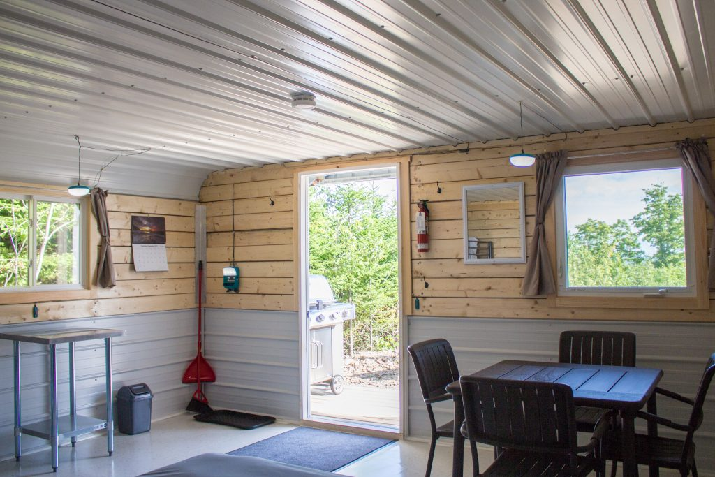 Interior of cabin showing a door mat, solar charging station and lights, broom and dustpan, garbage bin, calendar, mirror, fire extinguisher, windows with blackout curtains, dining table for four people and door leading to a porch with BBQ